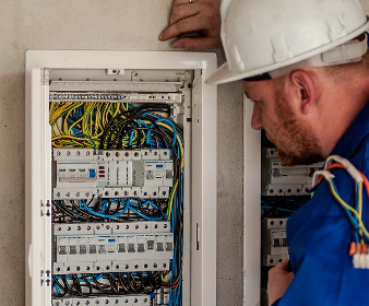the electrician stands next to the fuse box